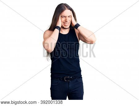 Young adult man with long hair wearing goth style with black clothes with hand on head, headache because stress. suffering migraine.
