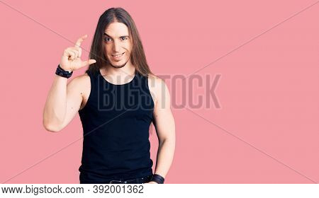 Young adult man with long hair wearing goth style with black clothes smiling and confident gesturing with hand doing small size sign with fingers looking and the camera. measure concept.
