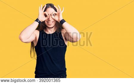 Young adult man with long hair wearing goth style with black clothes doing ok gesture like binoculars sticking tongue out, eyes looking through fingers. crazy expression.