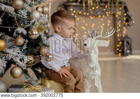 Happy Boy Laying On Floor With Christmas Gifts In Decorated Room