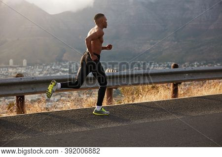 Sideways Shot Of Athletic Man Covers Long Distance, Runs On Empty Road, Has Early Morning Run On Hil