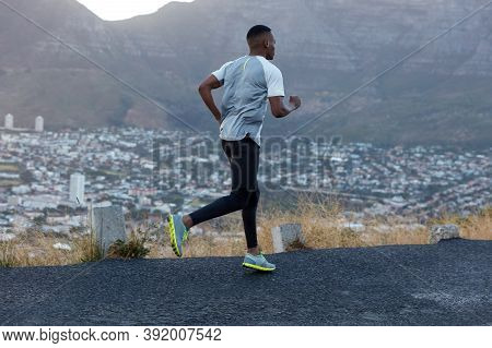 Photo Of Sportsman In Casual T Shirt, Black Leggings And Trainers, Runs Quickly Along Mountain Road,