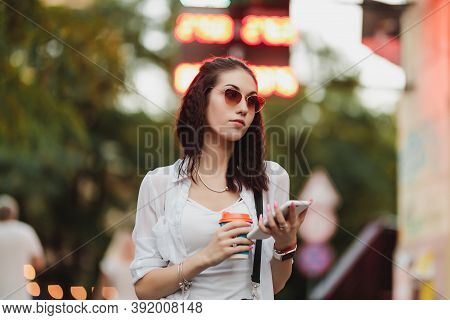 A Woman In Sunglasses Walks With Coffee On The Street.