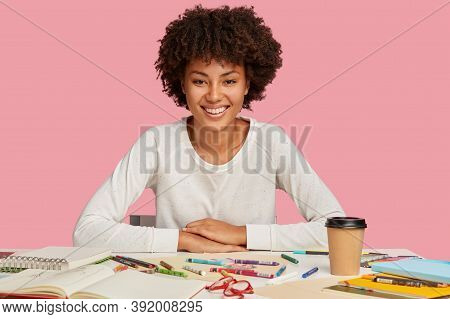 Isolated Shot Of Hilarious Dark Skinned Woman Has Afro Haircut, Dressed In Casual White Jumper, Sits