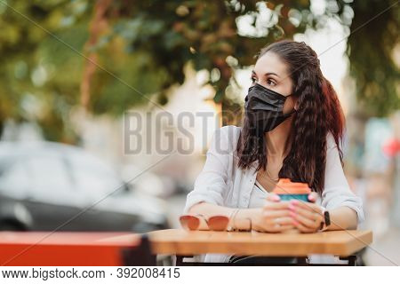 Quarantine Rate In A Cafe, A Young Woman In A Black Mask.