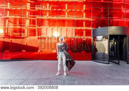Woman In Stylish Glasses On A Red Background.