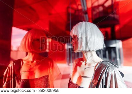 The Woman Looks At Herself Through The Reflection. Red Mirror