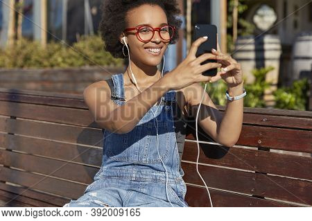 Positive Young Afro American Woman With Glad Expression, Has Videocall On Modern Cell Phone, Connect