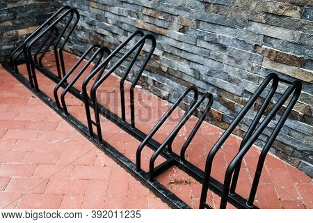 Empty Black Bicycle Rack During Pandemic. No People Out On Parking, Sitting At Home In Isolation. Us