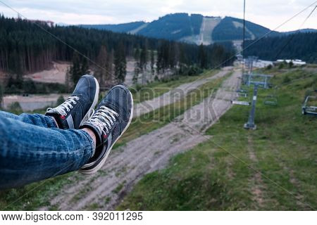 Male Legs In Jeans In The Air. Flying Up The Hill In The Carpathian Mountains. Feet In Shoes Riding