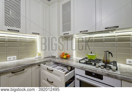White cozy and comfy contemporary classic kitchen interior with wooden furniture, some drawers are open
