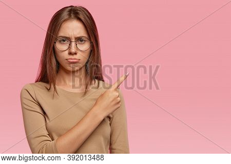 Displeased European Woman With Dark Hair, Purses Lower Lip, Has Dejected Facial Expression, Points A