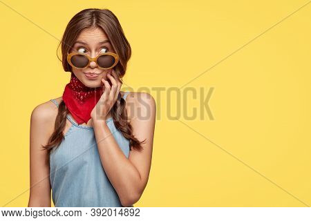 Puzzled Emotive Female Has Dark Hair Combed In Two Plaits, Wears Sunglasses, Bandana, Looks Aside Wi