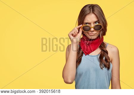Confused Uncertain Caucasian Woman Keeps Hand On Sunglasses, Raises Eyebrows, Wears Red Bandana, Has