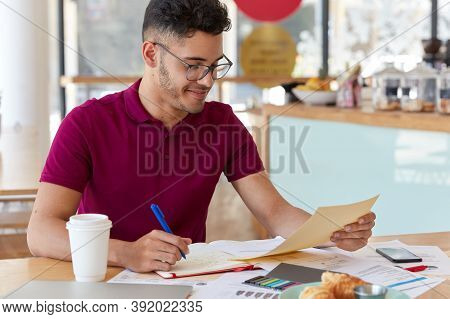 Photo Of Young Inexperienced Entrepreneur Records Information From Business Documents In Notepad, St