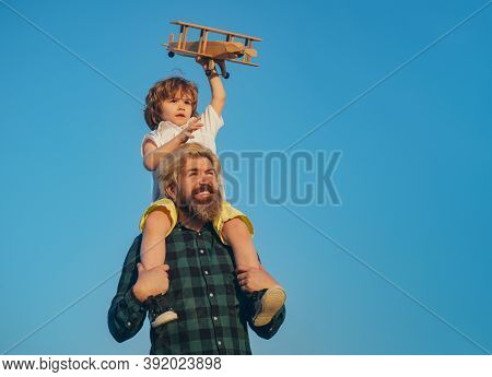 Happy Father Giving Shoulder Ride On His Shoulders. Father And Son Together. Boy Child Is Sitting On