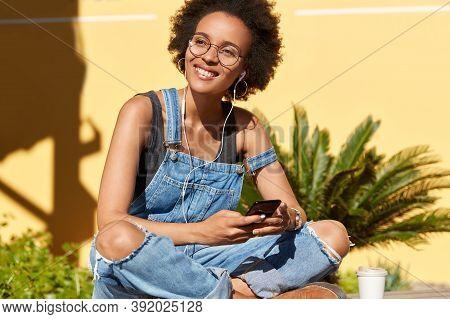 Joyful Girl Student Listens Audio Book In Earphones, Has Online Courses, Enjoys Spending Time In Tro