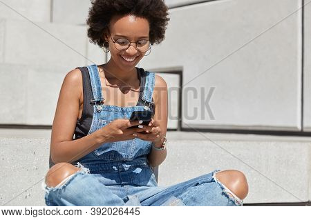 Happy Dark Skinned Youngster With Curly Haircut, Reads Pleasant Text Message, Watches Funny Video, T