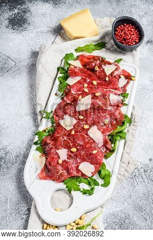 Carpaccio Of Marbled Beef. Raw Meat Black Angus. Gray Background. Top View