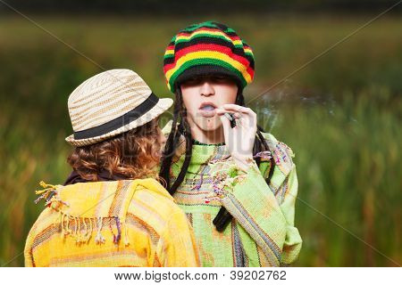 Young rastafarian couple against a nature background