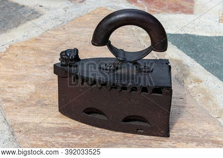 An Antique Cast Rusted Smoothing Iron With A Wooden Handle Working With Coal Of Charcoal As A Heat S