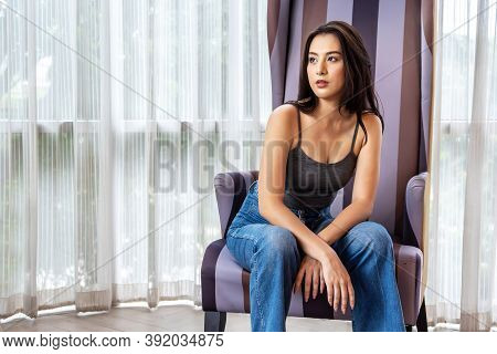 Young Beautiful Asian Woman Relax Sitting In Big Chair In The Room. Summer Fashion And Vacation Conc