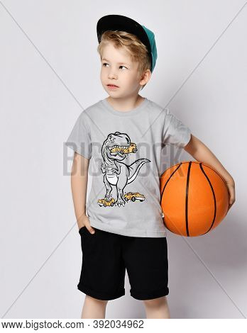 Self-confident Sporty Blond Kid Boy 6-7 Y.o. In Cap, Blue T-shirt With Dinosaur Eating Cars Print An