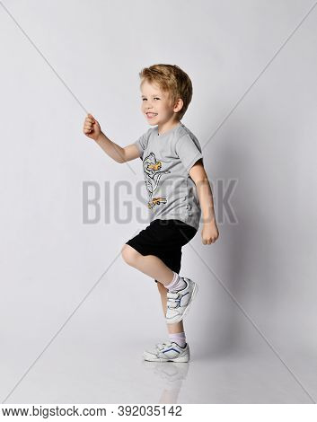 Cheerful Laughing Frolic Active Blond Kid 6-7 Y.o. Boy In Blue T-shirt And Black Shorts Plays He Is