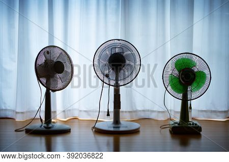 Off season gathering. Three off season household cooling fans in a empty room, unplugged, by a window with curtain.