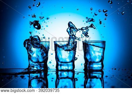 Strong Alcoholic Drink In Dammed Glasses With Ice On A Black Reflective Background. Splashes On A Bl