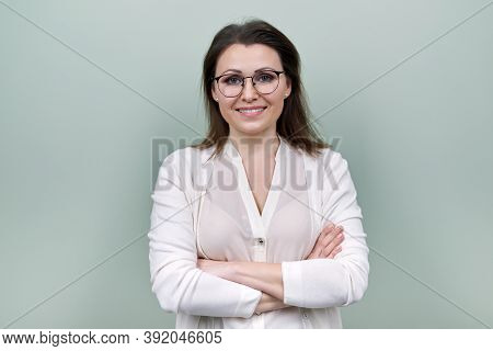Middle Aged Smiling Happy Woman In Glasses With Crossed Arms Over Green Background. Confident Mature