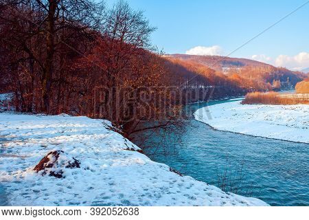 River In The Winter Scenery. Mountain Landscape On The Sunny Day. Trees On The Snow Covered River Ba