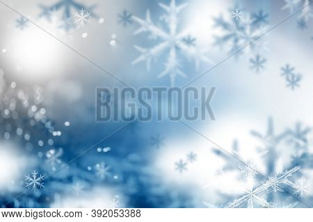 Magic holiday blue background with snowflakes. Blurred bokeh of Christmas lights.