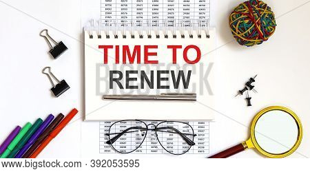 Notepad With The Text Time To Renew On Light Background, Near Glasses And Office Tools