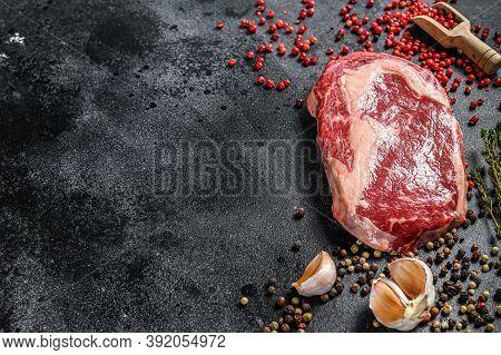 Raw Fresh Marbled Meat Steak Ribeye. Black Angus Rib Eye With Cooking Ingredients. Black Background.