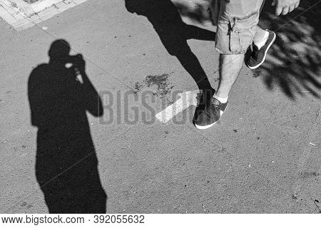 A Shadow Of A Street Photographer Sealing The Legs Of A Man Walking Against A Painted Arrow. Street