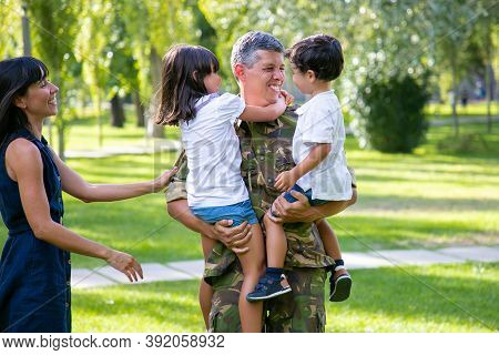 Happy Military Father Meeting With His Children And Wife After Military Mission Trip, Holding Kids I
