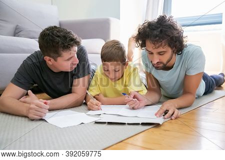 Couple Of Homosexual Parents Helping Focused Boy With School Home Task, Lying On Floor At Home, Writ