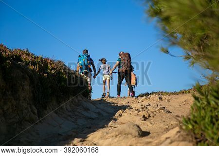Family Of Hikers With Backpacks Walking On Track. Parents And Two Kids Hiking Outdoors. Back View. H