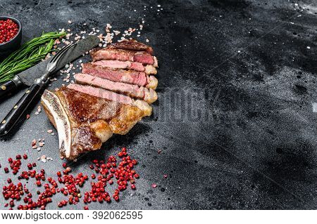 Grilled Cowboy Or Ribeye Beef Steak With Herbs And . Black Background. Top View. Copy Space