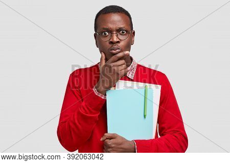 Photo Of Perplexed Indignant Black Man Holds Chin, Carries Folders And Papers, Stares At Camera With