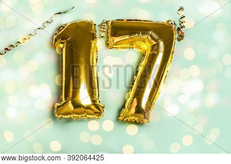 Decoration For Seventeen Birthday Party. Golden Balloon In Form Of 17 Number On Blue Background. Spa