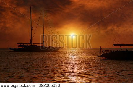Silhouette Nautical Vessels Luxury Yachts At Cala Saona Bay In Formentera During Bright Cloudy Sunse