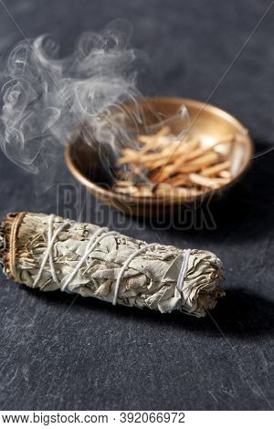 occult science and supernatural concept - white sage and cup with smoking matches