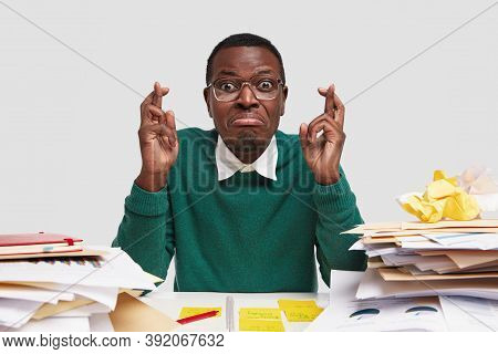 Hopeful Miserable Student Sits At Desk With Crossed Fingers Gesture, Dressed In Casual Clothes, Wear