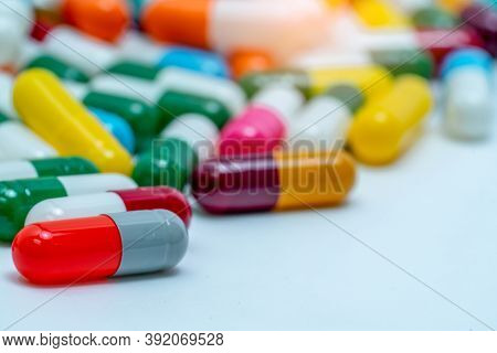 Selective Focus On Orange-gray Antibiotic Capsule Pill On Blurred Background Of Colorful Capsule Pil