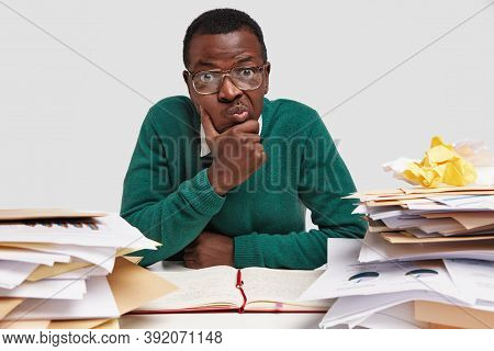Education And Exam Preparation Concept. Confused Dark Skinned Hipster Keeps Hand Under Chin, Sits At