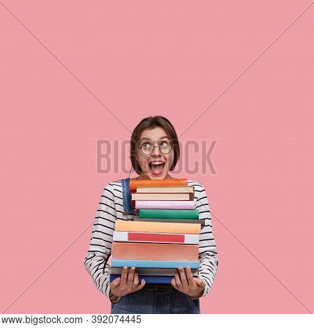 Studio Shot Of Joyful European Woman Wears Round Spectacles, Holds Many Books, Opens Mouth From Exci