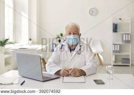 Senior Experienced Doctor In Uniform Sitting Near Laptop During Videocall And Online Meeting