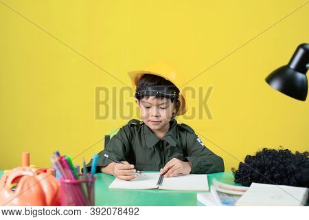 Boy With A Helmet Doing Homework, Learning Concept.